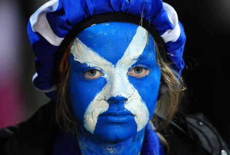 A Scottish fan with a painted face looks