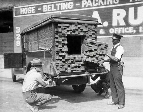 A federal agent inspects a 'lumber' truck after smelling alcohol during the prohibition period, Los Angeles, 1926. Historical Pics.