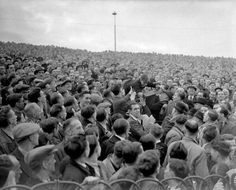 A young Chelsea fan is passed over the crowd to the front for a better view in a game against Arsenal. 1947. Historical Pics.