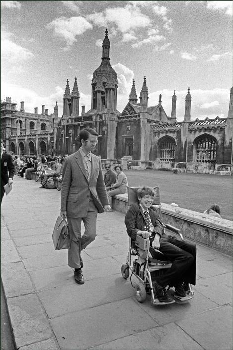 Stephen Hawking in his wheelchair in front of university buildings, Cambridge, 1977. Classic Pics.