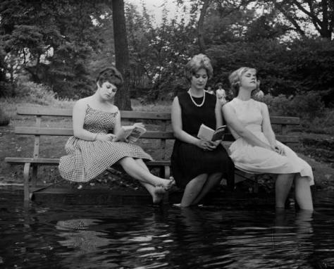 Three women keep cool during a heat wave by moving a park bench into the water in Central Park, New York, 1961.  History in Pictures.