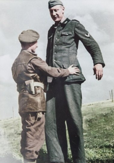 British corporal taking the surrender of a tall german soldier, 1944. Classic Pics.