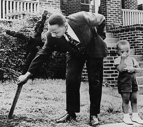 Martin Luther King com seu filho removendo uma cruz queimada em seu quintal, 1960.