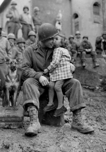 9th Armored Division technician with a little French girl on Valentine's Day, 1945. History in Pictures.