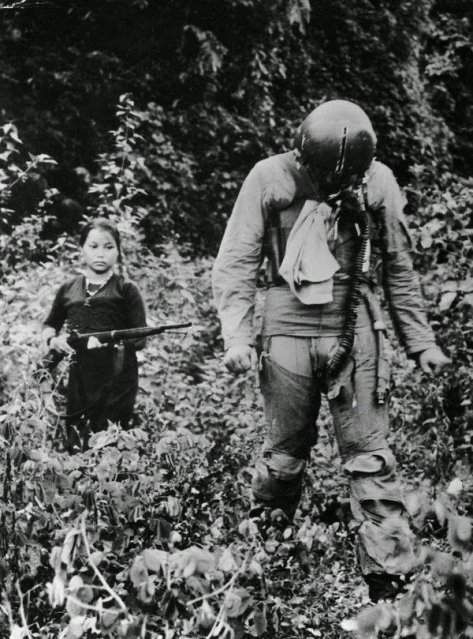 A US Air Force Lieutenant held captive by a young North Vietnamese girl soldier, 1967. Classic Pics.