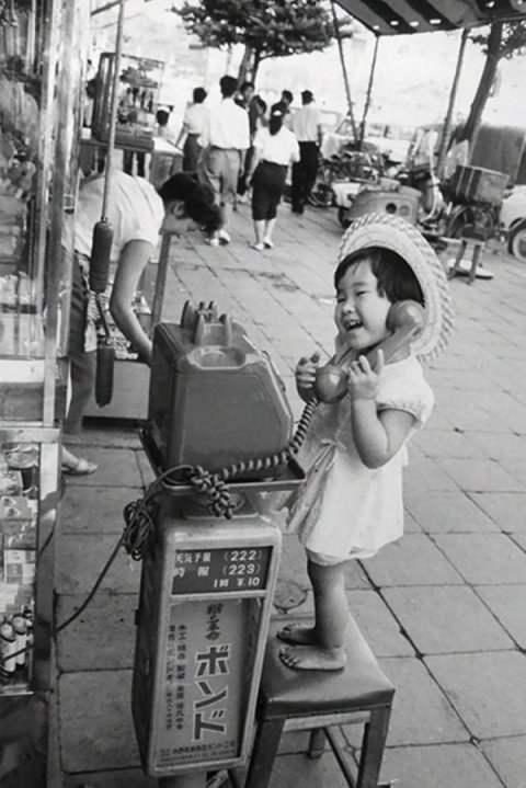 A little girl having fun pretending to talk on the telephone, Japan, 1958. Photograph by Marc Riboud. History in Pictures.