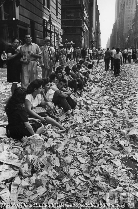 People sitting on curb among tickertape and confetti after celebrating the end of WWII on VJ Day in NYC, 1945. History in Pictures.