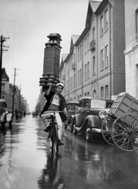 A delivery boy for a Tokyo Restaurant carries a tray of Soba Bowls. Classic Pics.