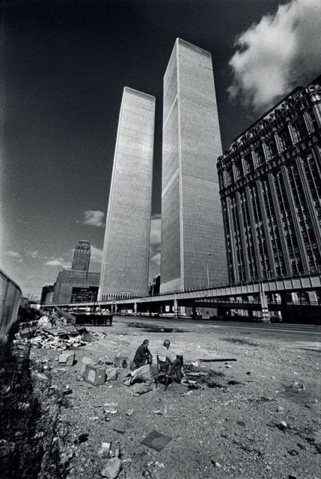 Two homeless men squat in the shadow of the recently completed World Trade Center, 1975. Old Pics Archive.