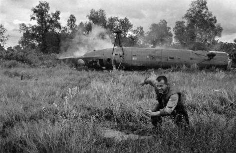 A U.S. crewman runs from a crashed helicopter,  South Vietnam, Dec. 11, 1962. Old Pics Archive.