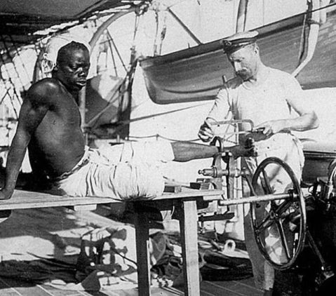 1800s – Late – British Soldier Removing Leg Irons off a Slave. Old Pics Archive.