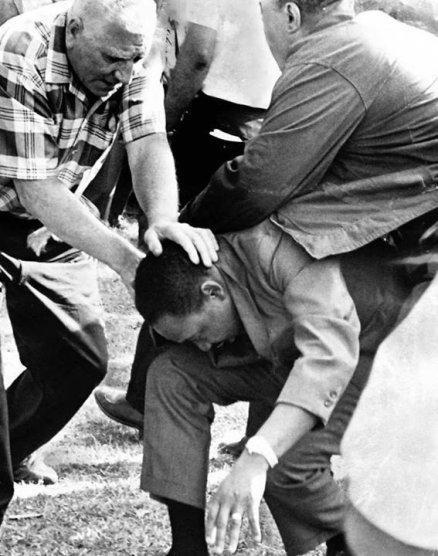 Dr. Martin Luther King Jr. é protegido por partidários depois de ser atingido por uma pedra na marcha pela habitação, em 1966. Fotos de fatos.