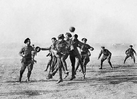 During the Christmas Truce of 1914,German and British soldiers play football in the no man_s land between trenches. Mood Vintage.