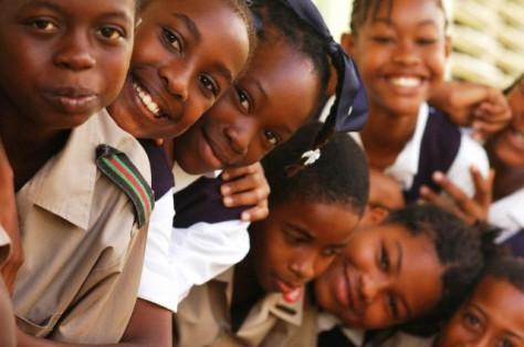Close-up of African schoolchildren smiling, standing one behind another, wearing school uniform