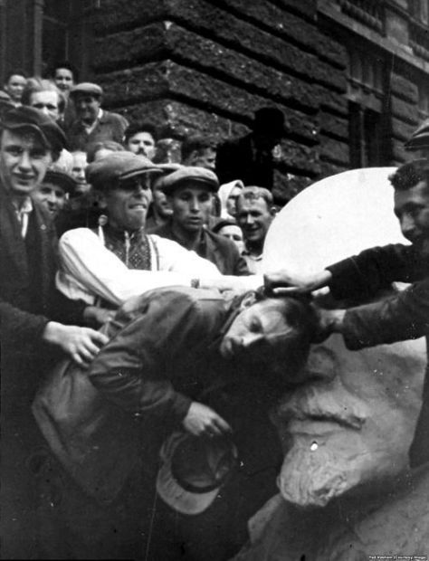 A Jewish man in western Ukraine being attacked by Ukrainians next to a bust of Lenin during nazi occupation, 1941. Old Pics Archive.